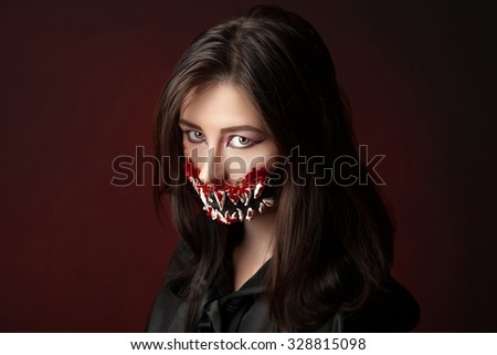 Character with big teeth and black mouth. Professional make up for horror film (faceart, bodyart, aqua grim), cosmetics. Realistic photo. Can be used for Halloween party, studio horror, milena, milina - stock photo