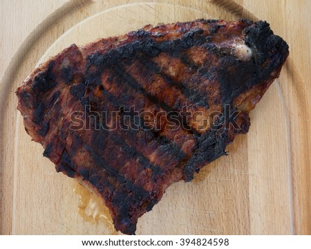 Charbroiled steak on a wooden cutting board. - stock photo