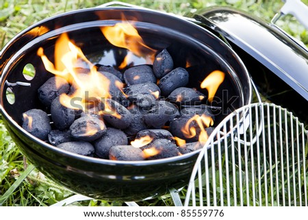 charcoal fire inside a barbeque in green grass - stock photo