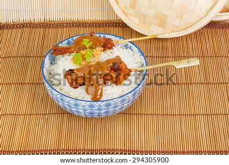 Charcoal grilled pork satay finished with soy sauce accompanied with rice, peanut sauce and fried onions - stock photo