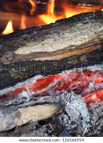 Charcoal, log and fire closeup - stock photo