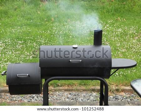 Charcoal offset smoker during backyard cookout - stock photo
