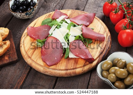 Charcuterie board with italian bresaola cured beef, grana padano cheese and rocket salad
