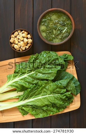 Chard leaves (lat. Beta vulgaris) on wooden board with a rustic bowl of chard soup and a small bowl of croutons, photographed on dark wood with natural light, overhead shot - stock photo