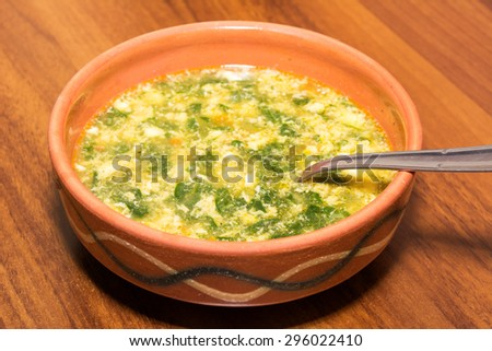 Chard soup in a rustic clay bowl on a wooden table - stock photo