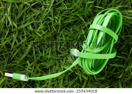 Charger wire green color put on grass background represent the mobile phone device equipment material related. - stock photo