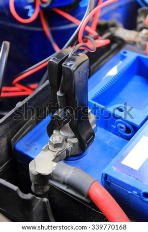 Charger with cables uses to charge old dead car battery - stock photo
