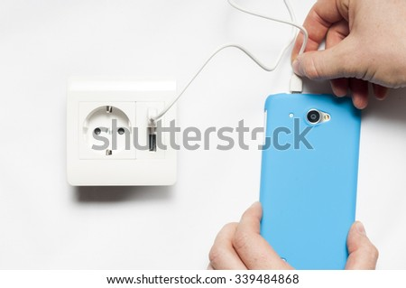 Charging. A man plugs  the smartphone to the socket, with two usb-charger ports. - stock photo