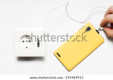 Charging. A man plugs  the smartphone to the socket, with two usb-charger ports.