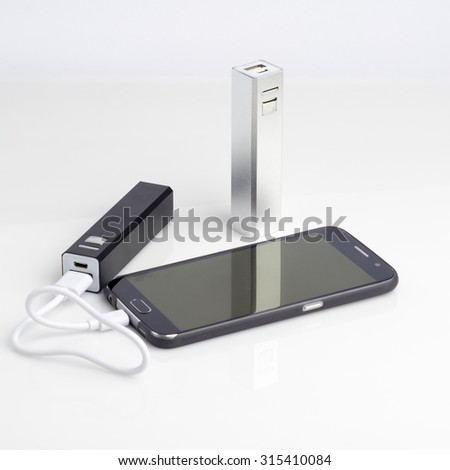Charging a smartphone from powerbank on white table - stock photo