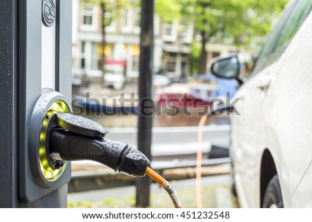 Charging an electric car - ecological way of driving - stock photo