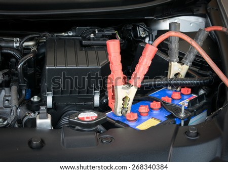 Charging battery car with electricity trough jumper cables - stock photo