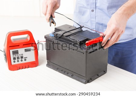 Charging car battery with electronic charger - stock photo