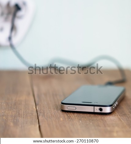 charging mobile phone on wooden table - stock photo