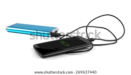 charging mobile phone with portable power bank - stock photo