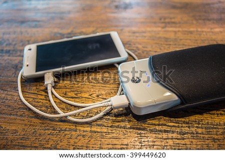 Charging smartphone with powerbank on wood. - stock photo