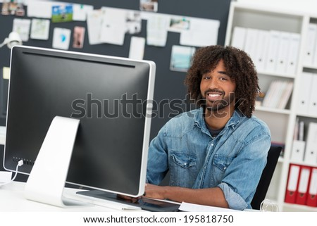 Charismatic African American businessman with an afro hairdo sitting at his desk with a desktop monitor smiling at the camera - stock photo