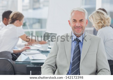 Charismatic businessman posing in the boardroom while colleagues are working behind - stock photo