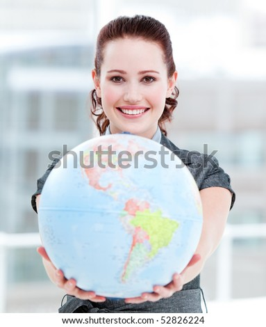 Charismatic businesswoman holding a terrestrial globe in the office