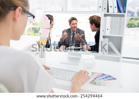 Charismatic chairman talking with his team against rear view of photo editor working on computer - stock photo