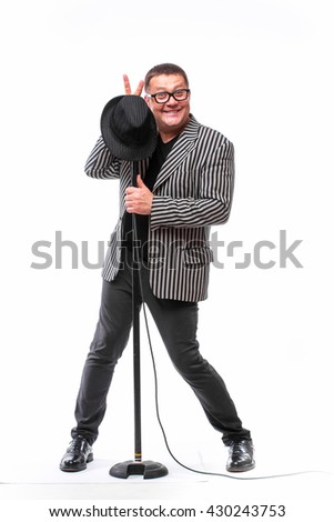 Charismatic handsome man in suit with black hat and microphone posing on white background