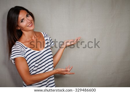 Charismatic lady 30-34 years old in casual clothing pointing against grey background