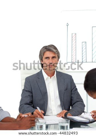 Charismatic mature businessman in a meeting with his team