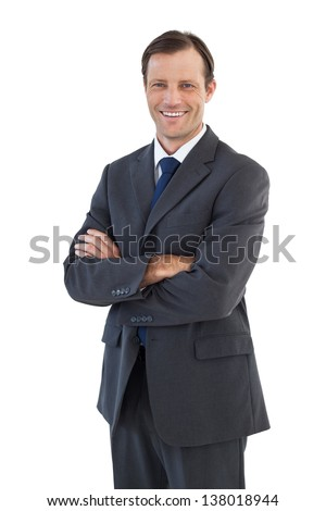 Charismatic smiling businessman standing with arms crossed on white background - stock photo