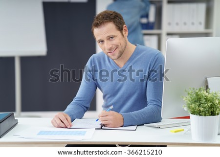 Charismatic young businessman looking up from his paperwork in the office to grin at the camera - stock photo