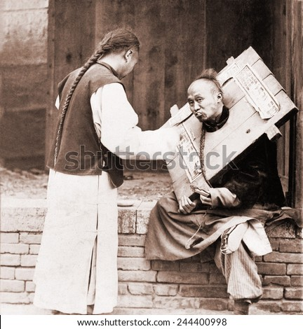 Charitable Chinese man feeding a criminal in a cangue. Petty criminals were sentenced to wear the canque, often for a couple of months, and display themselves in public places. Ca. 1905.