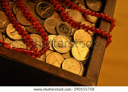 Charity during holy month of Ramadan. Close up of UAE Dirham coins in a vintage chest with prayer beads. - stock photo