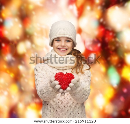 charity, happiness and love concept - smiling teenage girl in winter clothes with small red heart - stock photo