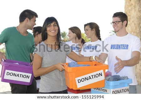 Charity: Happy group of volunteers collecting clothing donations  - stock photo