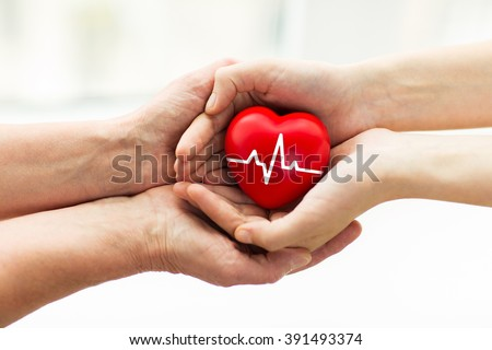charity, health care, donation and medicine concept - man hand giving red heart with cardiogram to woman