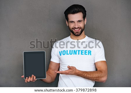 Charity is easier with technologies. Confident young man in volunteer t-shirt showing his digital tablet and looking at camera with smile while standing against grey background