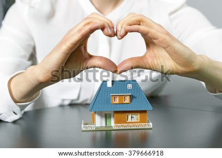 charity, real estate and family home concept - human hand in heart shape above small plastic house - stock photo