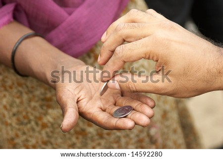 Charity. The man's hand gives alms in a female hand