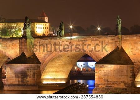 Charles bridge across Vltava river in autumn evening, Prague, Czech Republic - stock photo