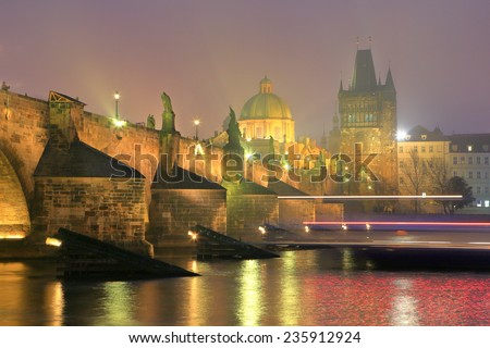 Charles bridge and distant towers and domes across Vltava river in foggy evening, Prague, Czech Republic - stock photo