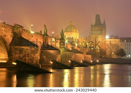 Charles bridge and Eastern bank of Vltava river in foggy autumn evening, Prague, Czech Republic - stock photo
