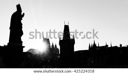 Charles Bridge at sunrise, Prague, Czech Republic. Dramatic statues and medieval towers. Silhouette photography style. Black and white - stock photo