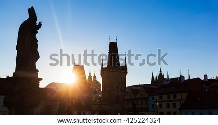 Charles Bridge at sunrise, Prague, Czech Republic. Dramatic statues and medieval towers. Silhouette photography style - stock photo