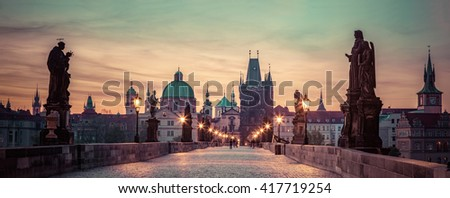 Charles Bridge at sunrise, Prague, Czech Republic. Dramatic statues and medieval towers. Unique panoramic view at dawn when there are almost no people on the bridge. - stock photo