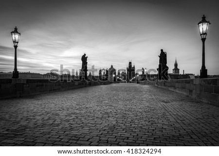 Charles Bridge at sunrise, Prague, Czech Republic. Dramatic statues and medieval towers. Unique view at dawn when there are almost no people on the bridge. Black and white - stock photo