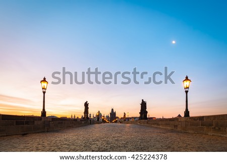 Charles Bridge at sunrise, Prague, Czech Republic. Dramatic statues and medieval towers. Unique view at dawn when there are almost no people on the bridge. - stock photo