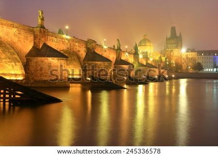 Charles bridge illuminated by yellow lights in foggy autumn evening, Prague, Czech Republic - stock photo