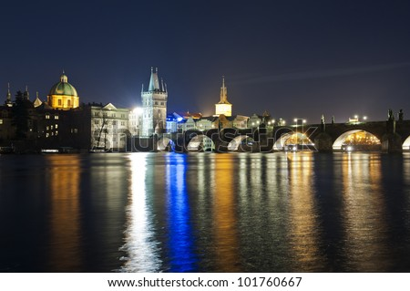 Charles bridge in Prague with various lights is reflecting in the river Vltava