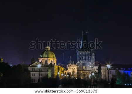 Charles bridge with tower and church in evening, Prague