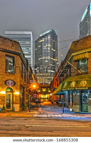 charlotte, nc  - December 8, 2013: Night view of a narrow alley street with restaurants in charlotte, nc - stock photo