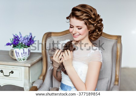 Charming and beautiful girl in white dress sitting in a chair, smiling and holding his little kittens, close-up - stock photo
